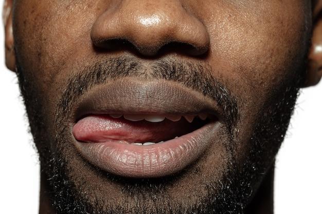 Gremassen. close-up van het gezicht van de mooie afro-amerikaanse jonge man, focus op mond.