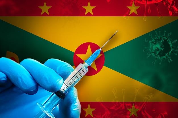 Grenada covid19 vaccinatiecampagne hand in een blauwe rubberen handschoen houdt de spuit voor de vlag