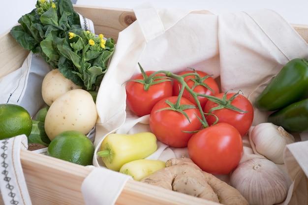 Grenen houten doos en katoenen eco tas met verse groenten. plastic vrij voor boodschappen boodschappen en bezorging. levensstijl zonder afval