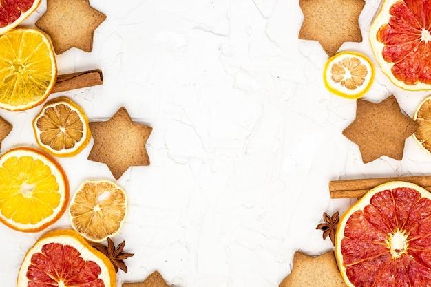 Grens van gedroogde plakjes van verschillende citrusvruchten peperkoek en kruiden op witte achtergrond met copyspace