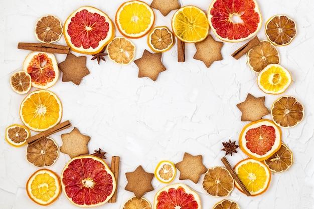 Grens van gedroogde plakjes van verschillende citrusvruchten peperkoek en specerijen frame op witte oppervlak met copyspace