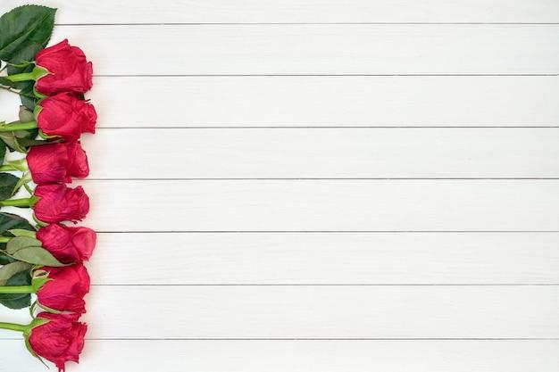 Grens van rode rozen op witte houten achtergrond. bovenaanzicht, kopie ruimte