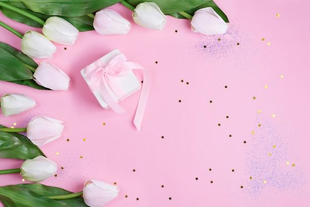 Grenskader met roze tulpen en geschenkdoos op roze sterren achtergrond, kopie ruimte