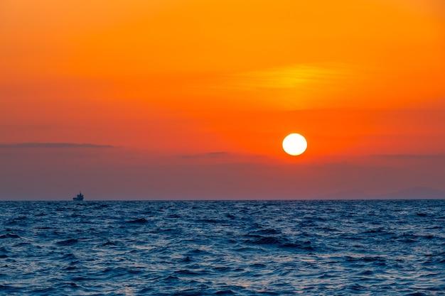 Grenzeloze zee. ongelooflijke oranje zonsondergang. klein vrachtschip aan de horizon