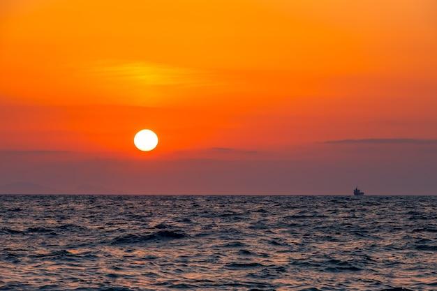 Grenzeloze zee. ongelooflijke rode zonsondergang. klein vrachtschip aan de horizon