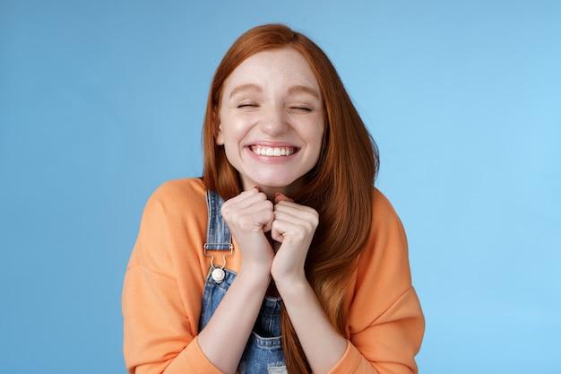 Gretig verheugend opgewonden mooi jong roodharig meisje ogen sluiten dromerig glimlachen ontvangen geweldig resultaat scholarchip triomferen vreugdevol grijnzend knijpen handen opgewonden staand blauwe achtergrond erg blij