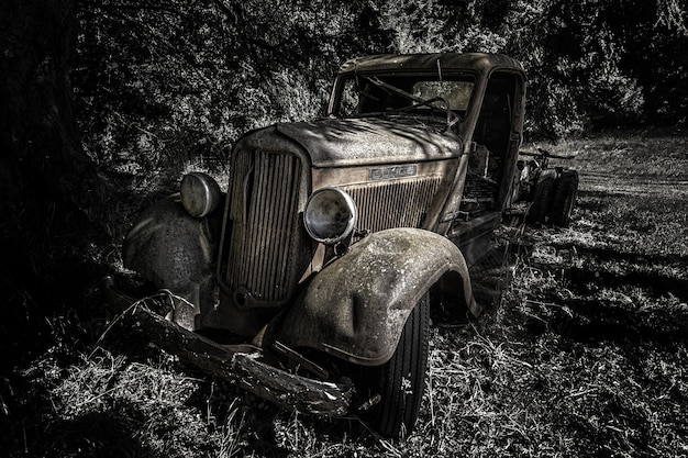 Greyscale die van een oude retro auto in het bos overdag is ontsproten