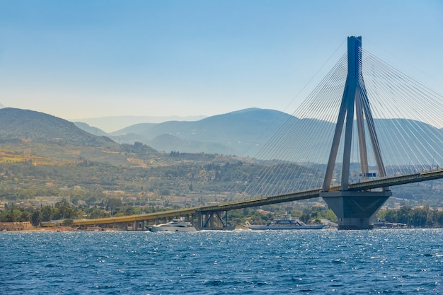 Griekenland. brug over de golf van korinthe op een zonnige zomerdag. modern motorjacht en veerboot