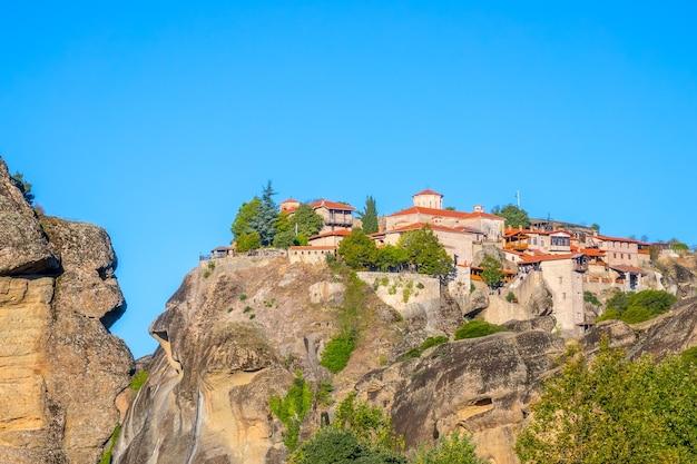 Griekenland. een heldere zomerdag in meteora. verschillende gebouwen van een rotsklooster met rode daken tegen een wolkenloze blauwe hemel