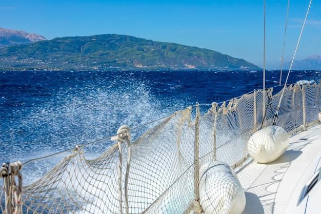 Griekenland. een zonnige en winderige dag in de golf van korinthe. linkerkant van een wit zeiljacht en waternevel