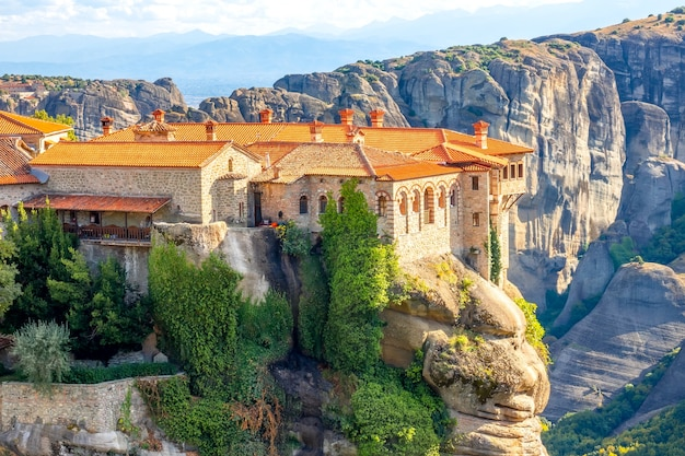 Griekenland. heldere zomerdag in meteora. verschillende gebouwen van een rotsklooster met rode daken tegen grote rotsen