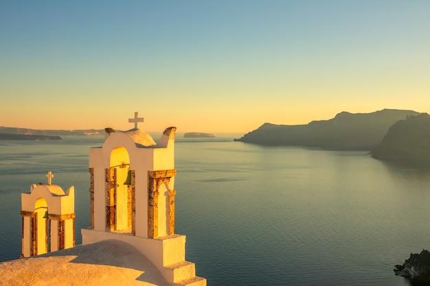 Griekenland. santorini eiland. kruisen op de griekse kerk in oia bij zonsondergang