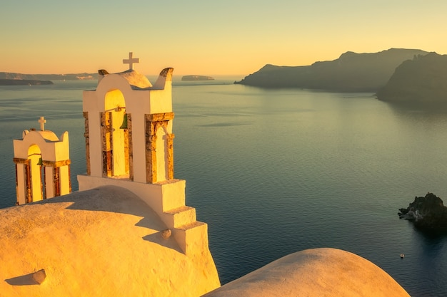 Griekenland. santorini. thira eiland. kruisen op de griekse kerk in oia bij zonsondergang