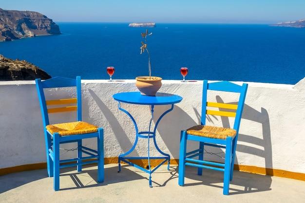 Griekenland. santorini. thira eiland. zonnig zeegezicht vanuit een café in oia. twee stoelen en twee glazen wijn
