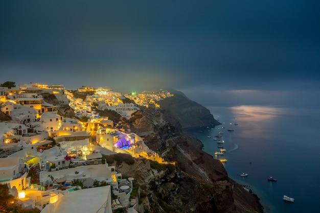Griekenland. thira-eiland. bewolkte nacht en stadslichten van oia