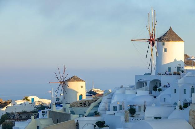 Griekenland. thira eiland. santorini. witte huizen en windmolens op een berghelling in de stad oia