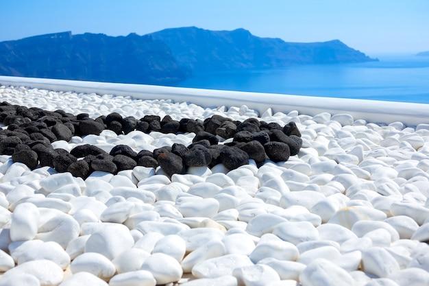 Griekenland. thira eiland. zonnige dag op santorini. zwarte en witte stenen op het terras met uitzicht op zee