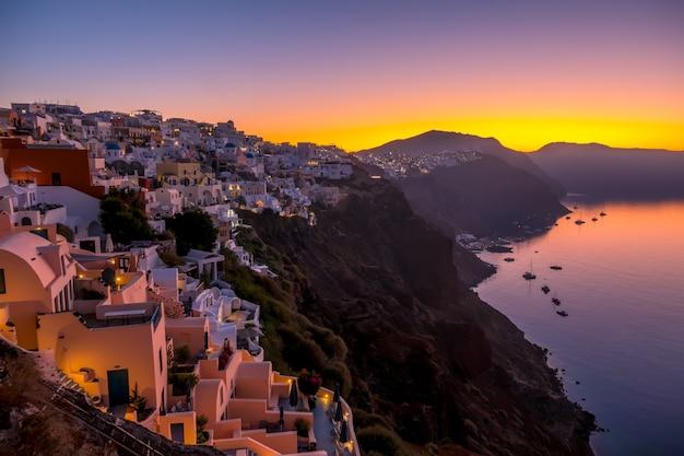Griekenland. vulkanisch eiland thira (santorini). wolkenloze ochtend boven de caldera. veel witte huizen van de stad oia aan de kant van een berg en een jacht in de haven
