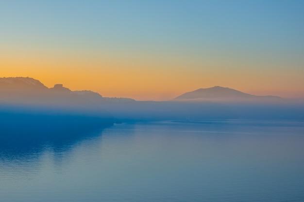 Griekenland. wolkenloze zonsopgang boven santorini. ochtendmist tegen de achtergrond van de zee en de rotsachtige kust