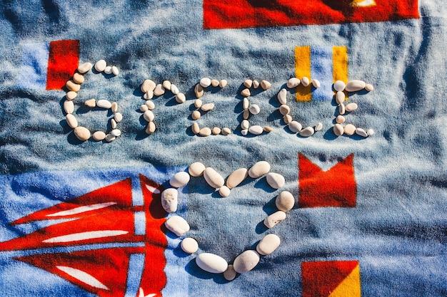 Griekenland woord gemaakt van witte kiezelstenen op blauwe handdoek