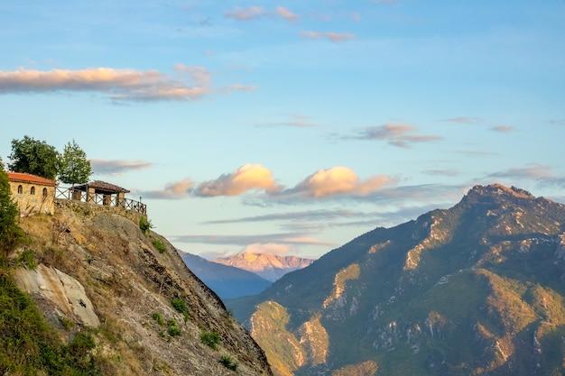 Griekenland. zomeravond in meteora. een prieel op een heuveltop en een rotsklooster met uitzicht op de bergtoppen