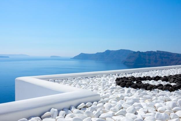 Griekenland. zonnige dag op santorini. thira eiland. zwarte en witte stenen op het terras met uitzicht op zee