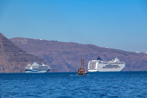 Griekenland. zonnige dag voor de kust van santorini. twee cruiseschepen met meerdere dekken en een oud driemasterschip