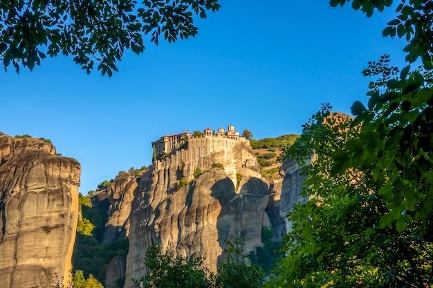 Griekenland. zonnige zomerdag in meteora. klooster op een hoge klif omgeven door gebladerte