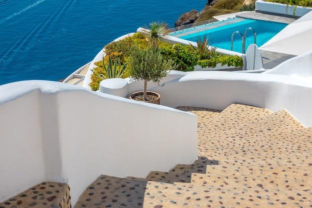 Griekenland. zonnige zomerdag in santorini. transparant zwembad in het resort en stenen trap op de helling van de caldera