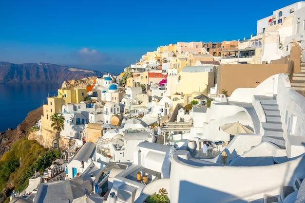 Griekenland. zonnige zomerdag in santorini. uitzicht op zee en oia gebouwen en terrassen met bloemen op de caldera