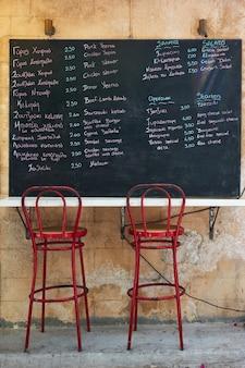 Grieks menu met prijs op bord in straatcafé op het eiland aegina, griekenland