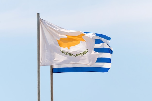 Griekse en cyprian vlaggen zwaaien tegen de blauwe hemel bij harde wind