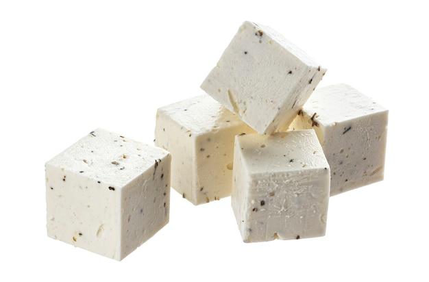 Griekse feta-blokjes met kruiden en specerijen, in blokjes gesneden zachte kaas geïsoleerd op een witte achtergrond