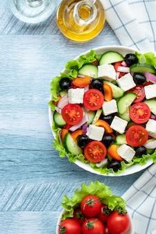 Griekse groentesalade met cherrytomaatjes, komkommers, fetakaas, olijven en gekruid met olie. wit geruit servet op een blauwe houten tafel. bovenaanzicht. plat leggen. gezonde voeding, een vegetarisch dieet.