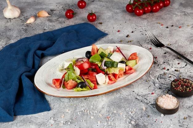 Griekse groentesalade met fetakaas, grijze achtergrond