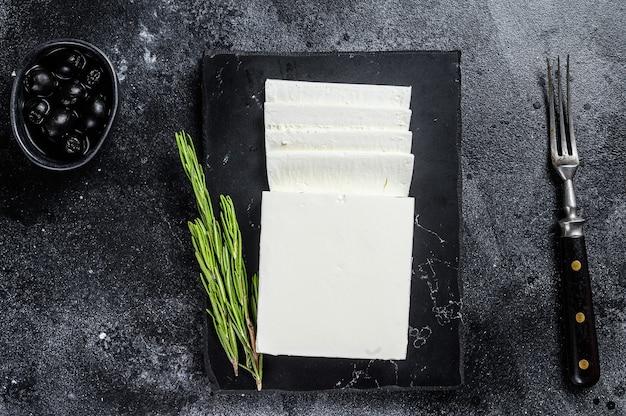 Griekse kaas feta met rozemarijn en olijven. zwarte achtergrond. bovenaanzicht.