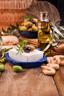 Griekse kaas feta met tijm en olijven. brood en jonge olijftak