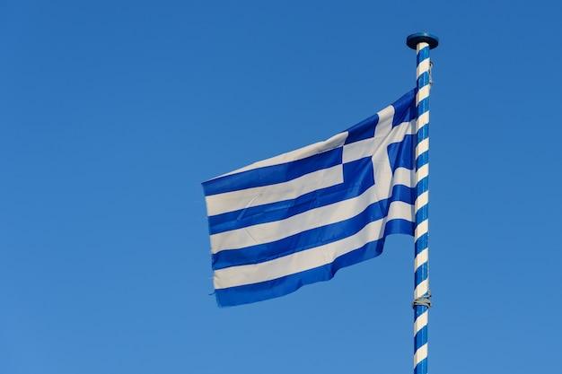Griekse nationale vlag zwaaien op blauwe hemelachtergrond, griekenland.