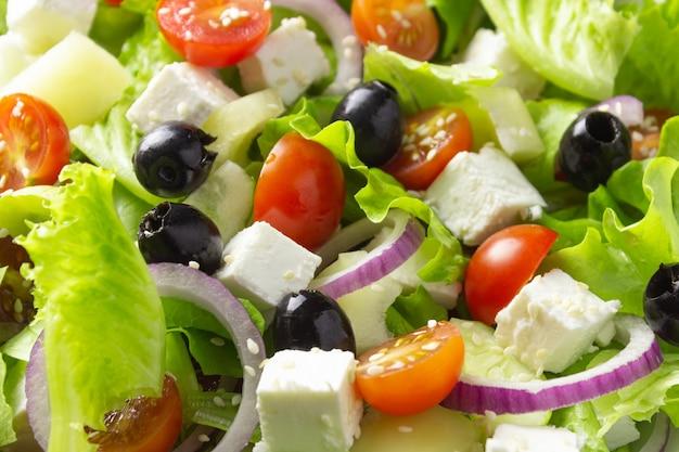 Griekse salade, close-up. achtergrond van plantaardige salade. gezond vegetarisch eten.
