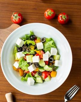 Griekse salade in de witte plaat met tomaten van boven