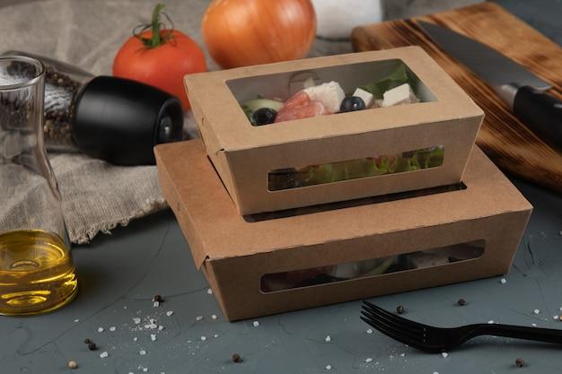 Griekse salade in een ambachtelijke doos voor bezorging