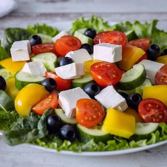 Griekse salade ingrediënten en voorbereiding, gesneden groenten close-up, evenwichtig dieet concept