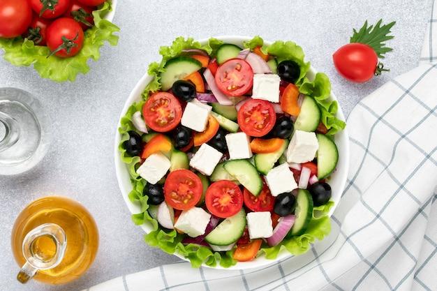 Griekse salade met fetakaas, cherrytomaatjes, komkommers, olijven en op smaak gebracht met olie. wit geruit servet op grijze tafel. bovenaanzicht. gezonde voeding, vegetarisch eten. gehakte groenten close-up.