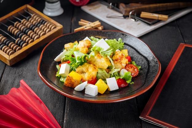 Griekse salade met gebakken vis en kaas op de zwarte houten