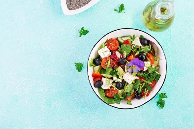 Griekse salade met komkommer, tomaat, paprika, sla, groene ui, fetakaas en olijven met olijfolie
