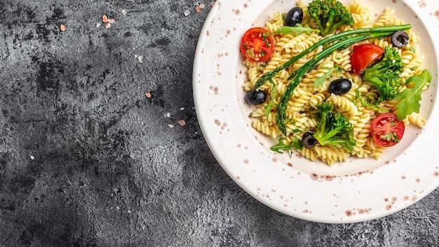 Griekse salade met pasta. kom fusili pastasalade met verse groenten. lang bannerformaat, bovenaanzicht.