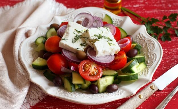 Griekse salade met tomaten, fetakaas, komkommers, uien en olijven