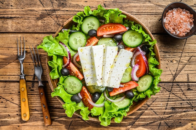Griekse salade met verse groenten en fetakaas. houten achtergrond. bovenaanzicht.