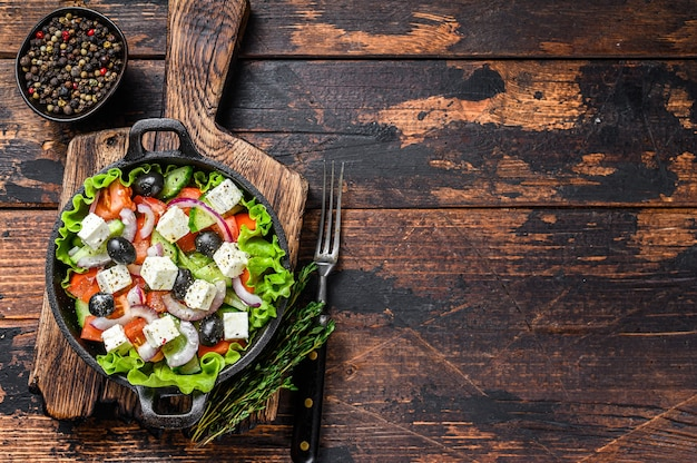 Griekse salade met verse groenten en fetakaas in een pan. donkere houten achtergrond. bovenaanzicht. ruimte kopiëren.