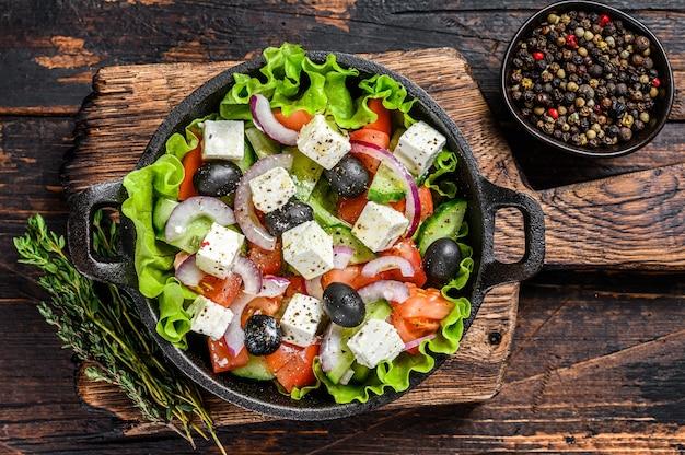Griekse salade met verse groenten en fetakaas in een pan. donkere houten achtergrond. bovenaanzicht.